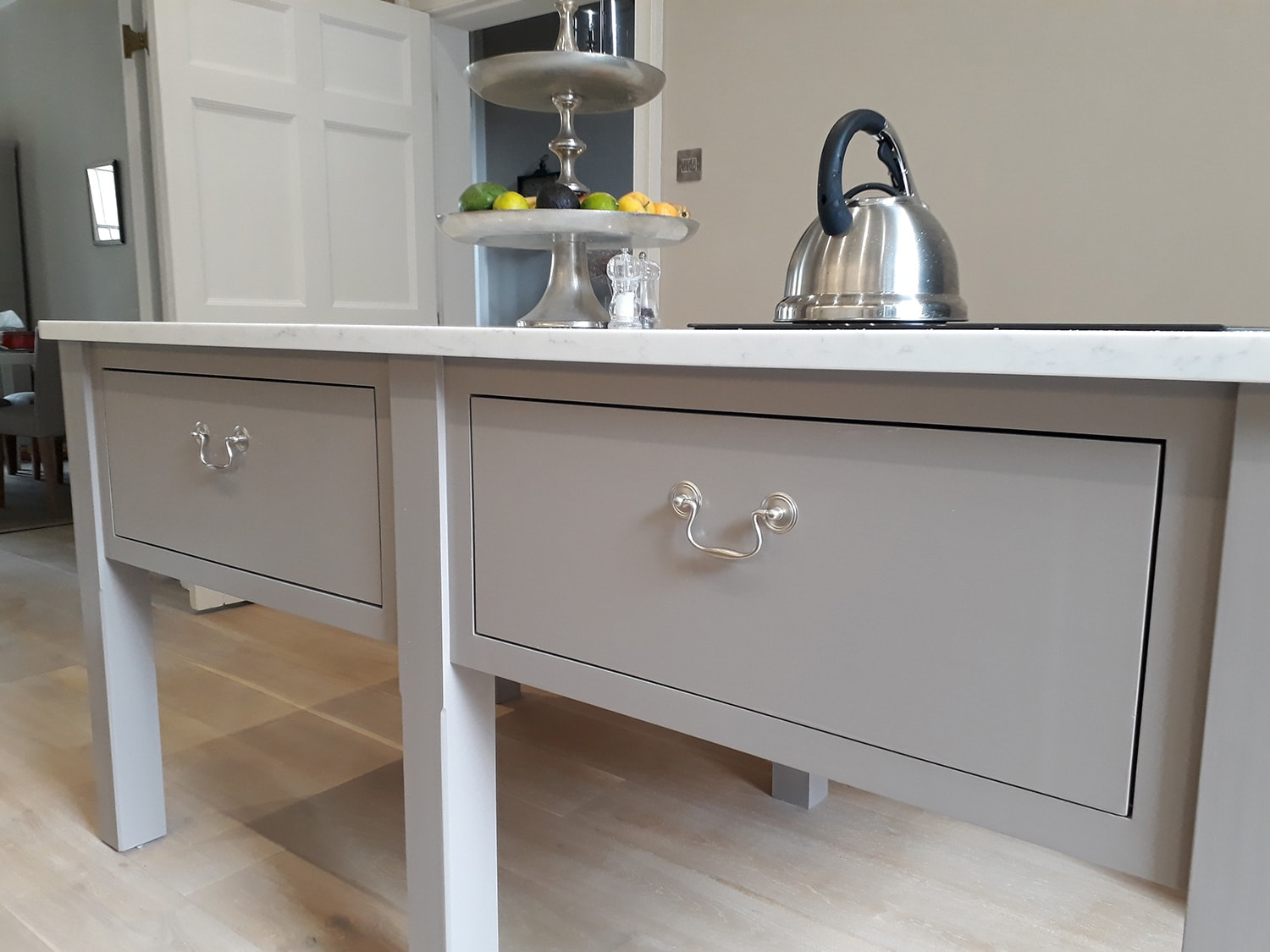 A bespoke kitchen design with cupboards and furniture